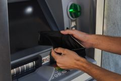 Man holding empty wallet near ATM machine. Concept of being broke stock photography