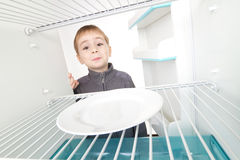 Boy and Empty Refrigerator Royalty Free Stock Images