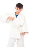 Boy engaged taekwondo and corrects belt Royalty Free Stock Photos