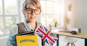Boy with English book in eyeglasses. Cute schoolboy in eyeglasses holding english book and british flag, looking to camera and smiling, education stock footage