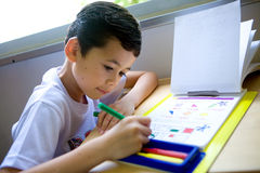 Boy engross doing his math coloring homework. Young boy engross doing his math coloring homework royalty free stock photo