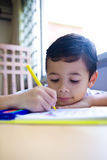 Boy engross doing his writing homework. Young boy engross doing his writing homework royalty free stock photo