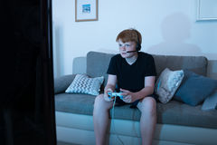 Boy Engrossed In Playing Videogames. Boy With Joystick Engrossed In Playing Videogames At Home Stock Images