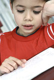 Boy engrossed while reading a book. Stock Photo