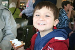 Boy Enjoying Binets. Young boy with powdered sugar all over his front after eating Binets at cafe Du Monde Royalty Free Stock Images