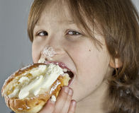 Boy enjoying a cream bun with almond paste Royalty Free Stock Photography