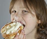 Boy enjoying a cream bun with almond paste. Getting cream on his noose Royalty Free Stock Photography
