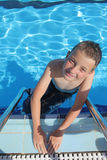 Boy enjoying a dip in the pool. Boy enjoys swimming in the pool during the summer Royalty Free Stock Photo