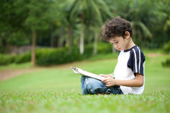 Boy enjoying his reading book in outdoor park Royalty Free Stock Photo