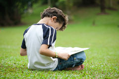 Boy enjoying his reading book in outdoor park. Young boy enjoying his reading book in outdoor park Royalty Free Stock Image