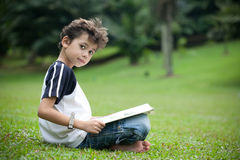 Boy enjoying his reading book in outdoor park. Young boy enjoying his reading book in outdoor park Stock Image