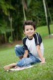 Boy enjoying his reading book in outdoor park. Young boy enjoying his reading book in outdoor park Stock Photography