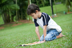 Boy enjoying his reading book in outdoor park. Young boy enjoying his reading book in outdoor park Royalty Free Stock Photo