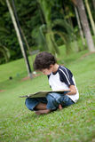 Boy enjoying his reading book in outdoor park. Young boy enjoying his reading book in outdoor park Royalty Free Stock Photography