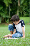 Boy enjoying his reading book in outdoor park. Young boy enjoying his reading book in outdoor park Stock Images
