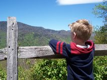 Boy enjoying mountain view. Young boy enjoying the beautiful mountain view from behind an old fence royalty free stock photo