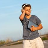 Boy enjoying music on tablet outdoors. Stock Image