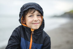 Boy enjoying the rain and having fun outside on the beach a gray rainy. A boy enjoying the rain and having fun outside on the beach on a gray rainy stock photography