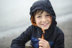 Boy enjoying the rain and having fun outside on the beach a gray rainy. A boy enjoying the rain and having fun outside on the beach on a gray rainy royalty free stock image
