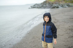 Boy enjoying the rain and having fun outside on the beach  a gray rainy Royalty Free Stock Images