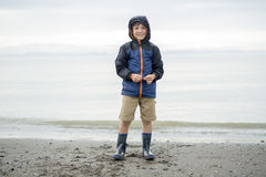 Boy enjoying the rain and having fun outside on the beach a gray rainy. A boy enjoying the rain and having fun outside on the beach on a gray rainy royalty free stock photo