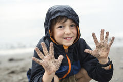 Boy enjoying the rain and having fun outside on the beach a gray rainy. A boy enjoying the rain and having fun outside on the beach on a gray rainy royalty free stock photography