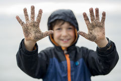 Boy enjoying the rain and having fun outside on the beach  a gray rainy Stock Photography