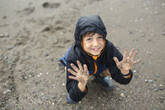 Boy enjoying the rain and having fun outside on the beach a gray rainy stock image