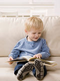 Boy enjoying reading a book Stock Photos