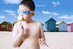 Boy enjoying a tasty ice cream at shore Royalty Free Stock Photo