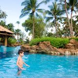 Boy enjoying a tropical swimming pool Stock Images
