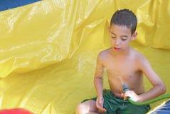 Boy enjoying a wet inflatable slide Stock Photography