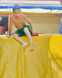 Boy enjoying a wet inflatable slide Royalty Free Stock Image