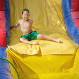Boy enjoying a wet inflatable slide Stock Photography