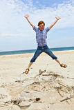 Boy enjoys  the beach and jumps Stock Image