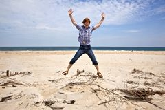 Boy enjoys  the beautiful beach and jumps Royalty Free Stock Image