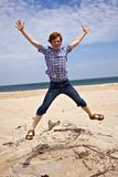 Boy enjoys  the beautiful beach and jumps Royalty Free Stock Photo