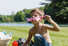 Boy enjoys blowing soap bubbles. Blond boy blowing soap bubbles in a sunny summer day Royalty Free Stock Photos