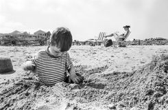 Boy enjoys digging at the beach Stock Photo