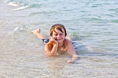 Boy enjoys lying at the beach in the surf Royalty Free Stock Images