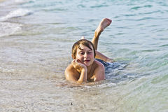 Boy enjoys lying at the beach in the surf Royalty Free Stock Photos