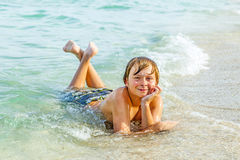 Boy enjoys lying at the beach in the surf Stock Photo
