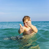Boy enjoys the ocean and shows Royalty Free Stock Images