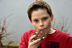 Boy enjoys pastry. Boy enjoys a piece of chocolate pastry Royalty Free Stock Image