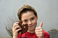 Boy enjoys pastry. Boy enjoys a piece of chocolate pastry, thumb up Stock Image