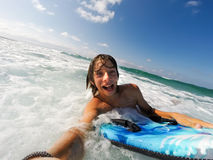 Boy enjoys riding the waves with a surfboard stock image