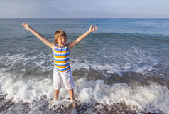 Boy enjoys the sea. Boy running through the water at the beach Stock Photo