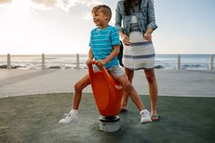 Mother and son on vacation. Boy enjoys sitting on a rotating chair near seafront. Woman with her son on a vacation enjoying near the sea Stock Photo