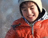 A boy enjoys a snow fight. A boy closes his eyes as a snow ball misses him Stock Photography
