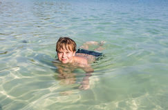Boy enjoys swimming in the  ocean Stock Photos